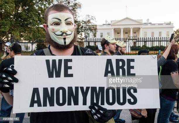 A protester wearing a Guy Fawkes mask stands near the White House during the Anonymous Million Mask March on the streets of downtown Washington DC on...