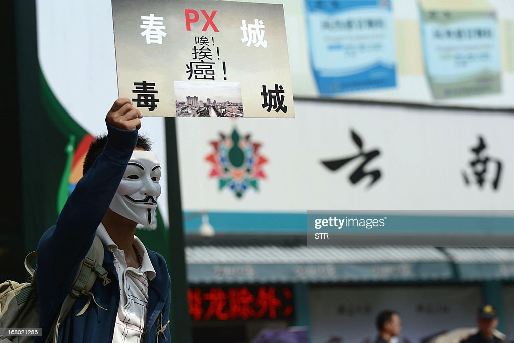 A protester wearing a Guy Fawkes mask, trademark of the anonymous movement and based on a character in the film V for Vendetta, holds a banner during a demonstration against plans for a factory to produce paraxylene (PX), a toxic petrochemical used to make fabrics, in Kunming, southwest China's Yunnan province on May 4, 2013. Hundreds of people took part in a street protest against a proposed chemical plant in southwest China on May 4, state media said, in an echo of earlier protests in other Chinese cities. CHINA
