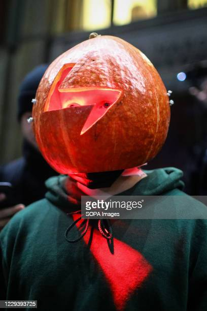 Protester wearing a Halloween-like pumpkin mask with cut-out lightning pattern, symbolising Women's Strike during the demonstration. The Polish...