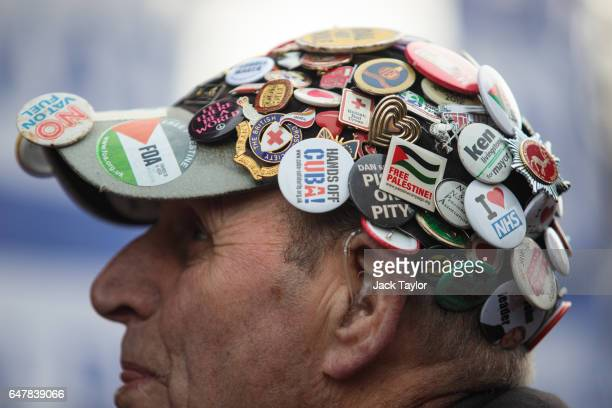 A protester wearing a hat covered in badges listens to a speaker in Parliament Square during a demonstration in support of the NHS on March 4 2017 in...