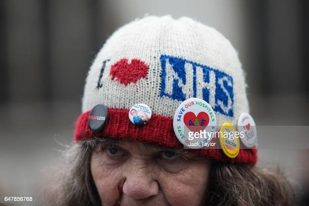 A protester wearing a hat with the NHS logo on it attends a demonstration Parliament Square in support of the NHS on March 4 2017 in London England...