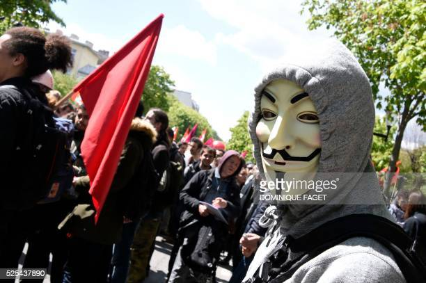 A protester wearing a hoodie and a Guy Fawkes mask takes part in a demonstration against proposed labour reforms in Paris on April 28 2016 Protesters...
