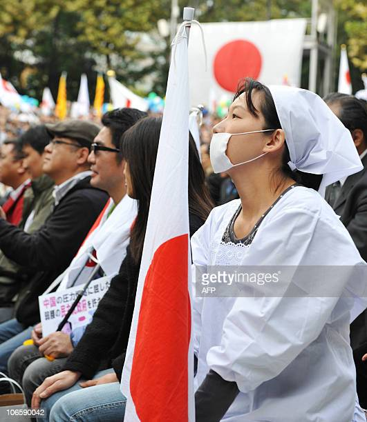 A protester wearing a Japanese chefs coat and holds a national flag during an antiChina protest rally in central Tokyo on November 6 2010 Japanese...