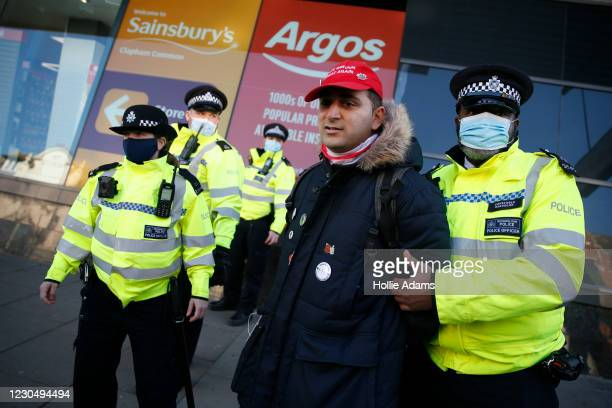 """Protester wearing a """"Make Britain Great Again"""" baseball cap is detained by Police on Clapham high street during the anti-lockdown demonstration on..."""