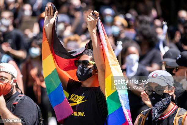 A protester wearing a mask and draped in the pride rainbow flag wears a shirt that says Blasian Black and Yellow with a Nike logo on it was part of...