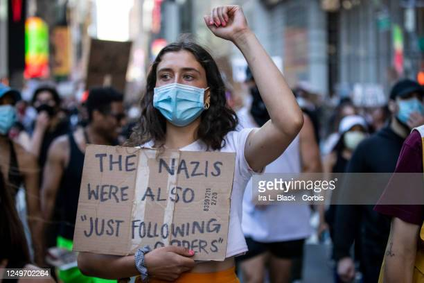 A protester wearing a mask and holding up a raised fist holds a sign that reads The Nazis Were Also Just Following Orders as they march through the...