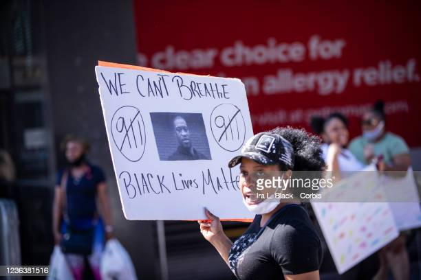 A protester wearing a mask around their neck holds a sign with a picture of George Floyd and saying We Cant Breathe and Black Lives Matter It also...