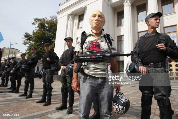 A protester wearing a mask depicting Russian President Vladimir Putin attends a protest outside the Ukrainian Parliament during the end of the fourth...