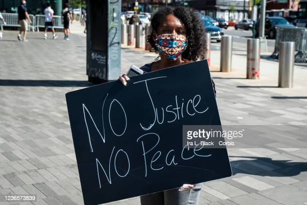 A protester wearing a mask holding a sign that says No Justice No Peace Protesters took to the streets across America after the killing of George...