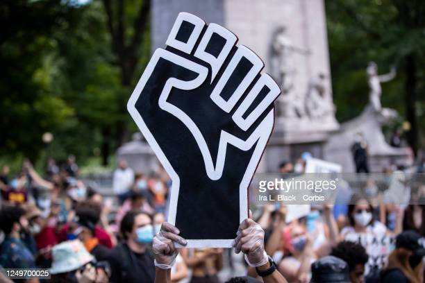 A protester wearing a mask holds a large black power raised fist in the middle of the crowd that gathered at Columbus Circle This was part of the...