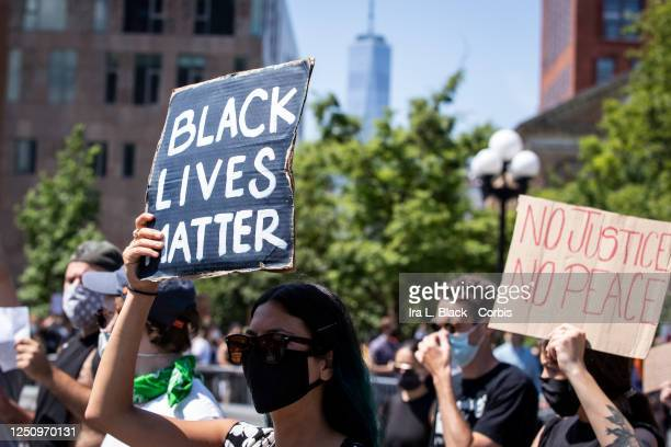 A protester wearing a mask holds a sign that says Black Lives Matter while another protester holds a sign that reads No Justice No Peace with One...