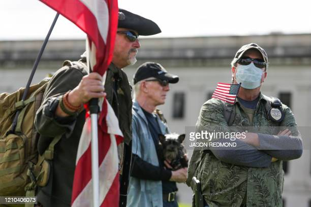 A protester wearing a mask holds a US flag during a demonstration against Washington state's stayhome order at the state capitol in Olympia...