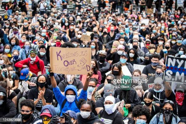 A protester wearing a mask holds up a sign that says Kneeling is Over Together We Stand with a drawing of a closed fist Protesters sat on the ground...