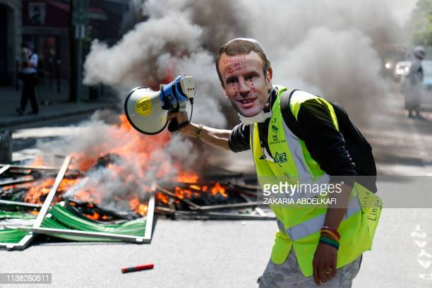 Protester wearing a mask of French President Emmanuel Macron crying stands next to a burning barricade during an anti-government demonstration called...