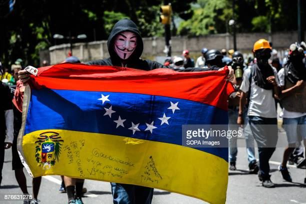 A protester wearing a mask of Guy Fawkes also known as the mask of anonymous holds a Venezuelan flag during a protest against President Nicolas...