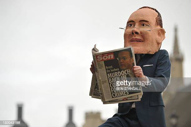 A protester wearing a mask of News International chairman James Murdoch the son of News Corp boss Rupert Murdoch poses with a mockup of a newspaper...