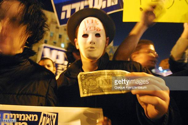 A protester wearing a mask outside Israel's Prime Minister Ariel Sharon's Jerusalem office holds a US one dollar bill accusing the PM of corruption...