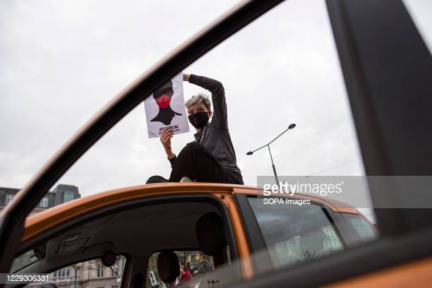 Protester wearing a mask sits on the roof a car and holds the poster of Women's Strike during the protest. Thousands of people took to the streets of...