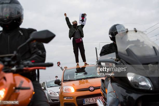 Protester wearing a mask stands on the roof of a car and gestures with a placard during the protest. Thousands of people took to the streets of...