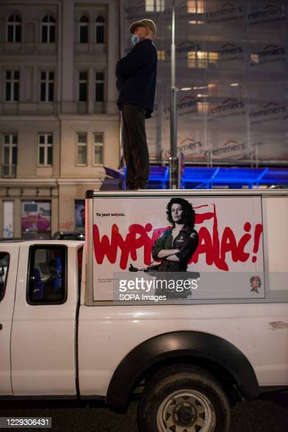 A protester wearing a mask stands on the roof of his car with Sigourney Weaver as Ellen Ripley image taped on the Vehicle during the protest...