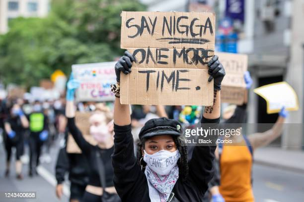 A protester wearing a mask that says I Can't Breathe and holding a handmade sign that says SAY NIGGA ONE MORE TIME marches down the streets of New...