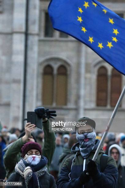 A protester wearing a mask waves an European flag during a demonstration against the government's new labour reform dubbed the slave law by the...