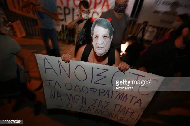 Protester wearing a mask with the image of Cypriot President Nikos Anastassiades hold a placard during an anti-corruption demonstration on October...