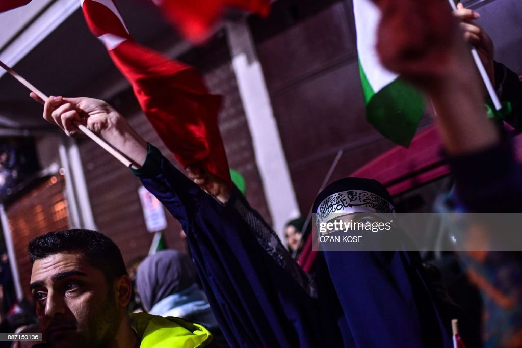 A protester wearing a niqab waves a flag during a demonstration against the US and Israel in front of the US consulate in Istanbul on December 6, 2017. Hundreds of people staged a protest outside the US consulate in Istanbul angrily denouncing the US president's move to recognise Jerusalem as the capital of Israel. Around 1,500 people gathered outside the well-protected compound close to the Bosphorus which was sealed off by police with barricades, an AFP correspondent said. /