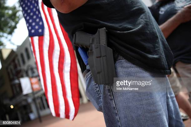 A protester wearing a pistol on his hip stands near the location where a car plowed into a crowd of protestors marching through a downtown shopping...