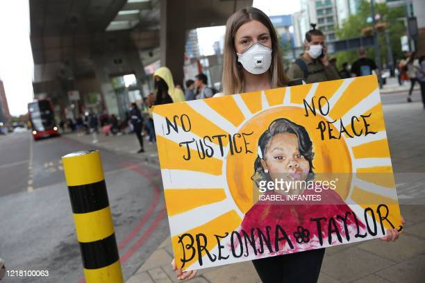 A protester wearing a protective face mask holds a placard as she goes to a demonstration outside the US Embassy in London on June 7 organised to...
