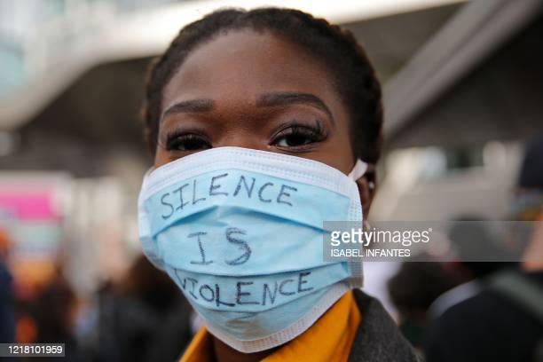 A protester wearing a protective face mask with a silence is violence slogan written on the fabric prepares to attend a demonstration outside the US...