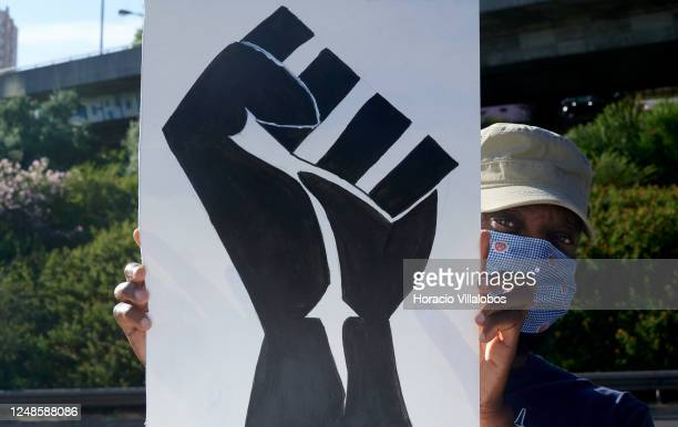 A protester wearing a protective mask holds up a placard with the Black Lives Matter fist symbol as Antifa members gather across the street from the...