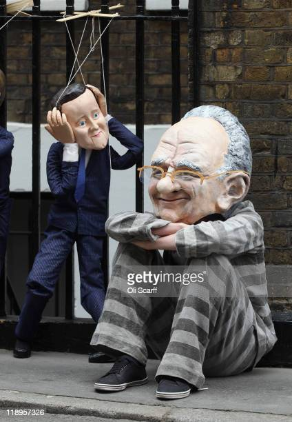 Protester wearing a Rupert Murdoch mask demonstrates with a David Cameron puppet outside the apartment of the News Corp CEO on July 13, 2011 in...