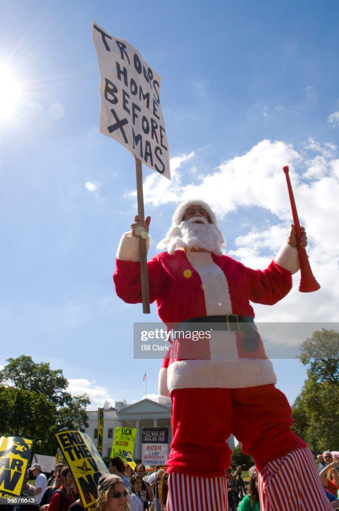 A protester wearing a Santa costume and walking on stilts calls for troops to come home before Christmas during the anti-war pre-march rally in Lafayette Square on Saturday, Sept. 15, 2007.
