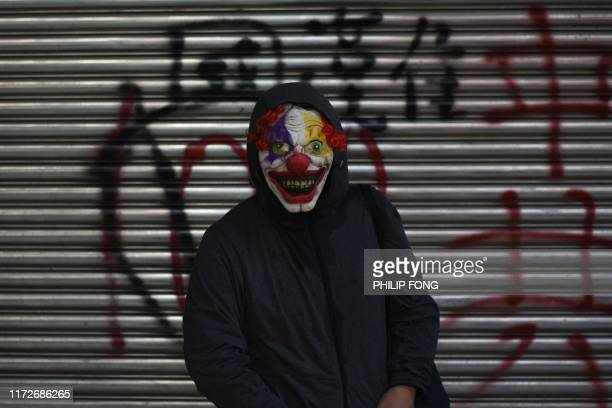 TOPSHOT A protester wearing a scary clown mask poses during a rally in Tsuen Wan district in Hong Kong on October 1 as the city observes the National...