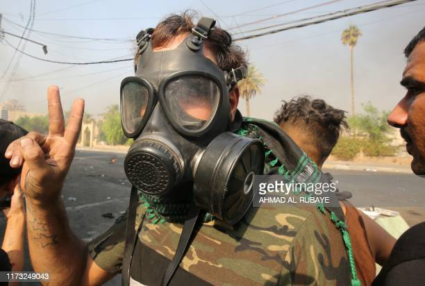 A protester wearing a security forces' gas mask flashes the victory gesture during clashes between protesters and riot police amidst demonstrations...