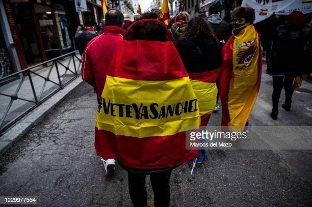 Protester wearing a Spanish flag with the words 'Sanchez go away now' during a demonstration marching to the Congress of Deputies to protest against...