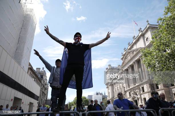 A protester wearing a St George's Cross face mask climbs on a barrier as farright linked groups gather around London's statues on June 13 2020 in...