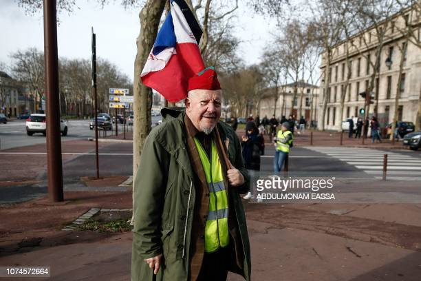A protester wearing a 'Yellow Vest' and holding a French flag stands in a street near the Chateau de Versailles in Versailles outside Paris on...
