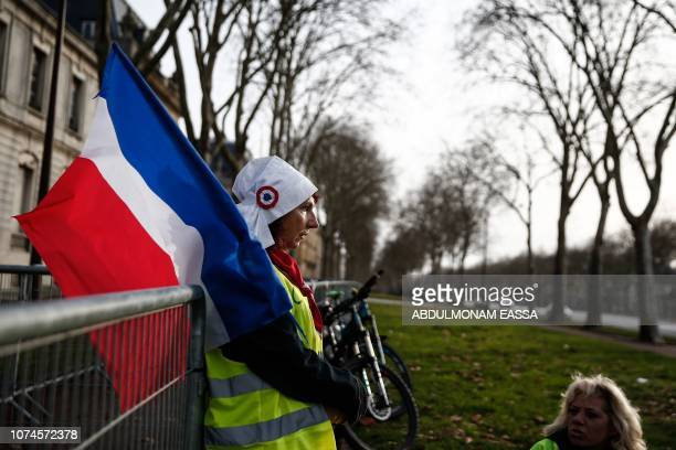 A protester wearing a 'Yellow Vest' and holding a French flag stands near the Chateau de Versailles in Versailles outside Paris on December 22 2018...