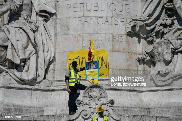 TOPSHOT A protester wearing a yellow vest and standing on the statue on Place de la Republique holds a placard referring to Esmeralda and Quasimodo...