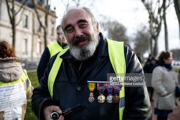 TOPSHOT A protester wearing a 'Yellow Vest' and wearing decoration poses in a street in Versailles outside Paris on December 22 2018 The 'Yellow...