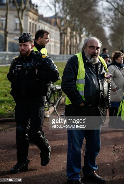 A protester wearing a 'Yellow Vest' and wearing decoration poses in a street next to police officer in Versailles outside Paris on December 22 2018...