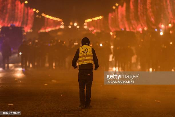 Protester wearing a Yellow Vest faces riot police during a demonstration of the 'Yellow Vests' against rising costs of living on the Champs Elysees...