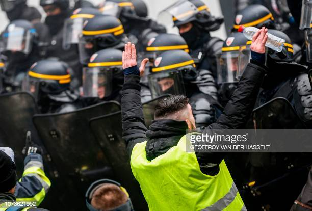 A protester wearing a yellow vest facesoff French riot police during a demonstration against rising costs of living blamed on high taxes in Paris on...
