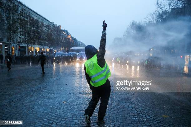 TOPSHOT A protester wearing a yellow vest gestures in front of police forces during a demonstration against rising costs of living blamed on high...