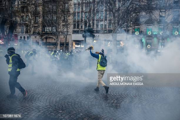 A protester wearing a yellow vest holds a bunch of flowers as he runs through smoke of tear gas during a demonstration against rising costs of living...