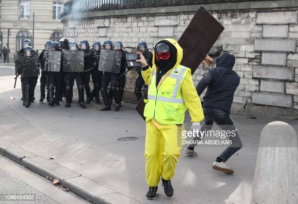 A protester wearing a yellow vest holds a mobile phone as a protester throws a wooden plank to French gendarmes near the National Assembly in Paris...