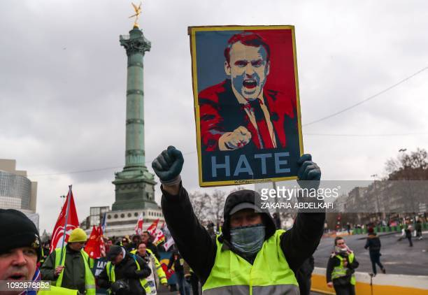 A protester wearing a yellow vest holds a placard depicting the French President and reading 'Hate' during a march on February 2 2019 on Place de la...
