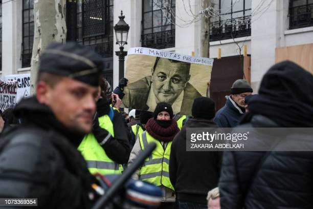 A protester wearing a yellow vest holds a placard picturing French humorist Michel Colucci aka Coluche and reading 'Hey Manu don't you 1000 quids'...